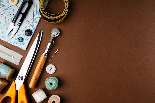 Composição plana leiga de acessórios de costura, tesouras, padrões em um fundo marrom, vista superior, espaço de cópia.