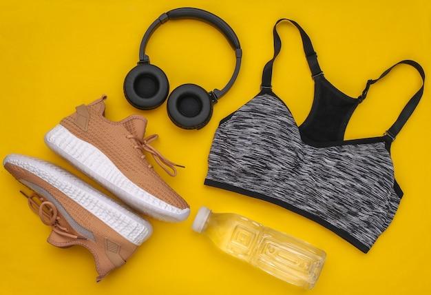 Composição plana leiga de equipamentos esportivos, roupas em fundo amarelo. fitness, esporte e conceito de estilo de vida saudável. vista do topo