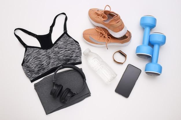 Composição plana leiga de equipamentos esportivos, roupas em fundo branco. fitness, esporte e conceito de estilo de vida saudável. vista do topo