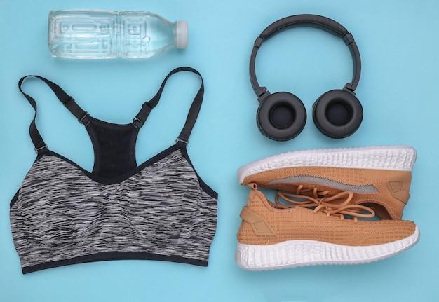 Composição plana leiga de equipamentos esportivos, roupas sobre fundo azul. fitness, esporte e conceito de estilo de vida saudável. vista do topo