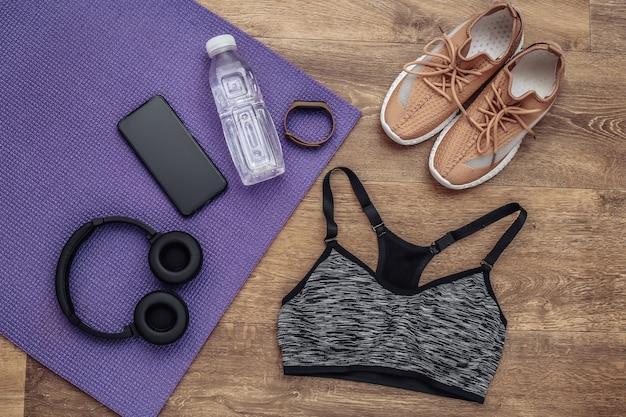 Composição plana leiga de equipamentos esportivos, roupas sobre um piso de madeira. fitness, esporte e conceito de estilo de vida saudável. vista do topo