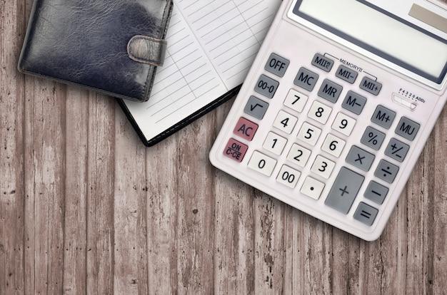 Composição plana leiga de escritório com calculadora, livro de endereços e bolsa preta