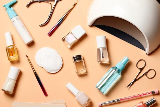 Composição plana leiga de ferramentas de manicure, lâmpada uv e esmaltes em um fundo rosa. lugar para texto.