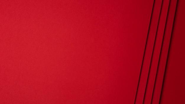 Composição plana leiga de fundo de folhas de papel vermelho