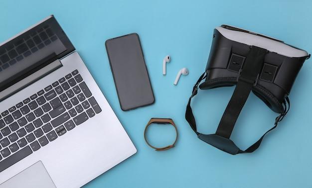 Composição plana leiga de laptop e dispositivos modernos sobre um fundo azul. vista do topo
