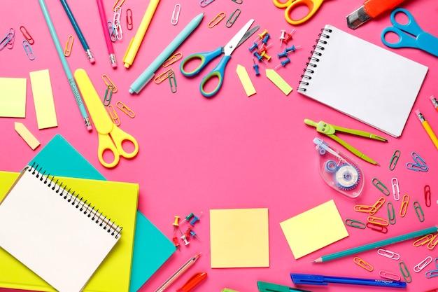 Composição plana leiga de material escolar em um fundo rosa. lugar para texto. vista do topo. dia do professor. de volta à escola.