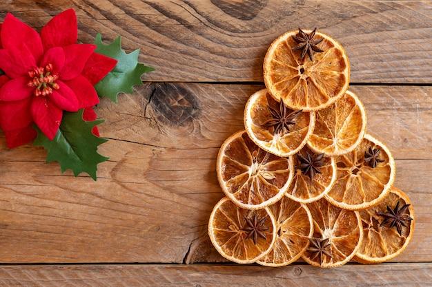 Composição plana leiga de natal. árvore de natal artesanal feita de laranjas secas e anis em fundo de madeira. férias de inverno, conceito de ano novo. ainda vida. vista superior, copie o espaço para o texto