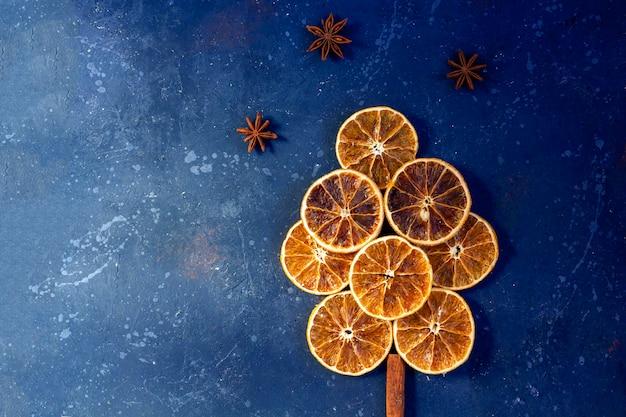 Composição plana leiga de natal. árvore feita de laranjas secas, canela e anis em fundo escuro. natal, férias de inverno, ano novo conceito. ainda vida romântica.