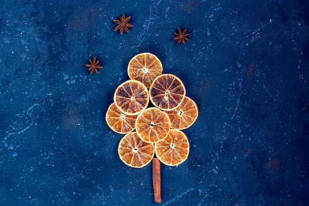 Composição plana leiga de natal. árvore feita de laranjas secas, canela e anis em fundo escuro. natal, férias de inverno, ano novo conceito.