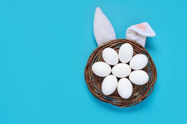 Composição plana leiga de orelhas de coelho de páscoa criativas sobre fundo azul, espaço para texto
