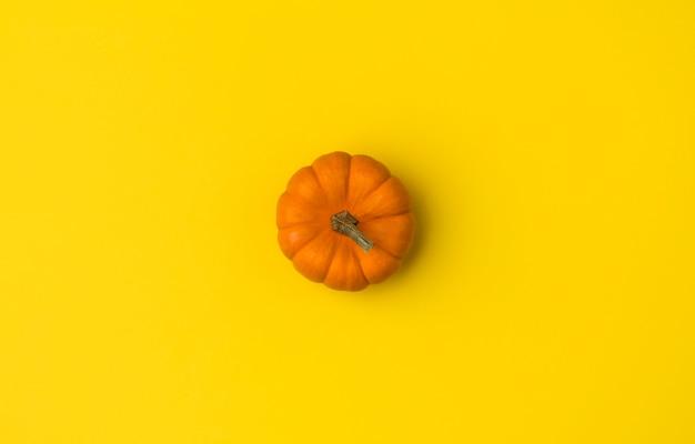 Composição plana leiga de outono. abóbora na mesa amarela.