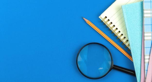 Composição plana leiga escolar com lápis de cadernos e lupa, estudante se prepara para o conceito de dias letivos, fundo azul com foto de espaço de cópia