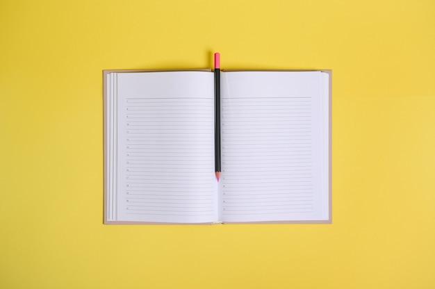 Composição plana leiga sobre fundo amarelo de um lápis de cor no meio de um organizador aberto com folhas brancas em branco limpas com espaço de cópia.