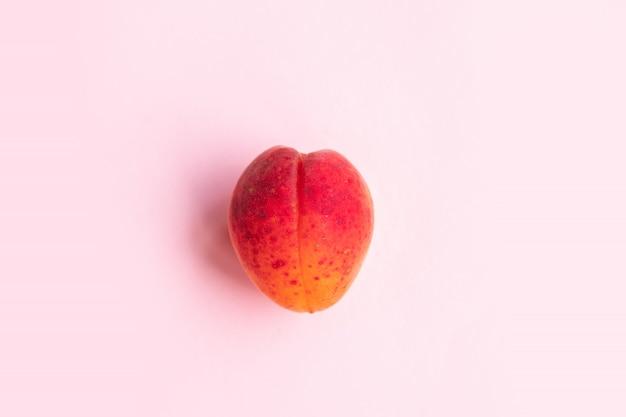 Composição plana maduro saboroso pêssego em um fundo rosa.