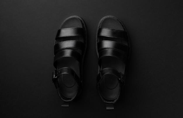 Composição plana monocromática mínima vista plana leiga com sandálias em preto