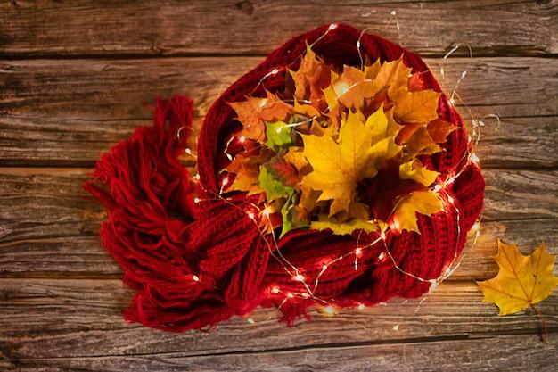 Composição quente de outono em tons de vermelho em um fundo de madeira com uma xícara de chá, guirlanda