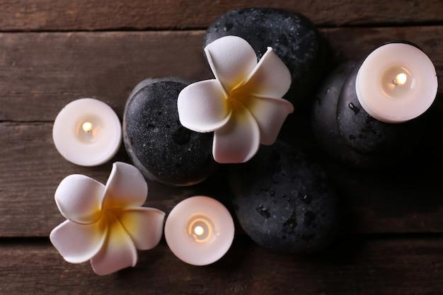 Composição relaxante com flores exóticas de fragipani, seixos e velas na parede de madeira