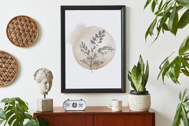 Composição retro moderna do interior da sala de estar com cômoda de teca de design, moldura preta, relógio, planta, decoração, parede branca e acessórios pessoais.
