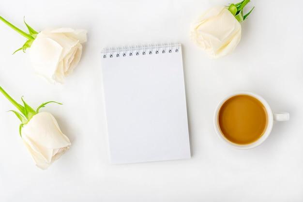 Composição romântica de flores de lat plana. caneca de café matinal para o café da manhã, caderno vazio com espaço de cópia para texto ou letras e rosas brancas