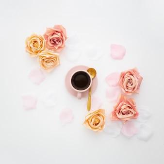 Composição romântica feita com uma xícara de café e rosas rosa