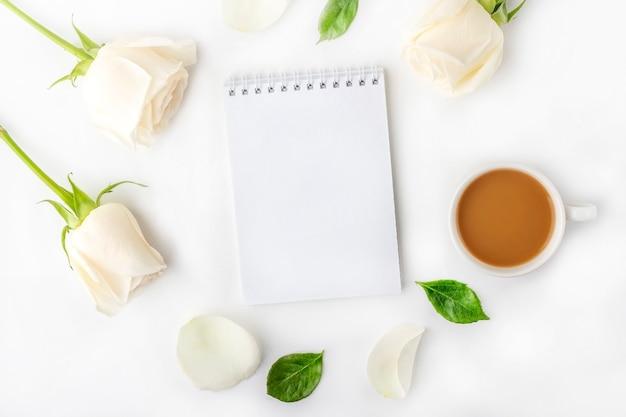 Composição romântica lat plana flores. caneca de café da manhã no café da manhã, caderno vazio com espaço de cópia de texto ou letras e rosas brancas.