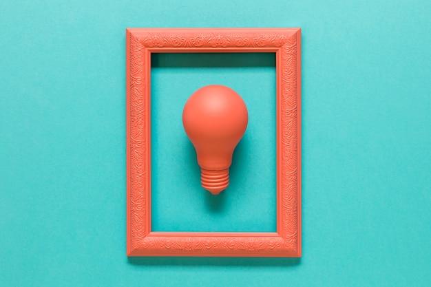 Composição rosa com lâmpada no quadro na superfície azul