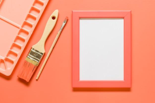 Composição rosa com moldura em branco e ferramentas de desenho na superfície colorida