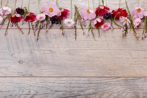 Composição rosa flores roxas em placas de madeira. flores silvestres no fundo da mesa de madeira artesanal. pano de fundo com espaço de cópia, vista plana, vista superior. conceito de dia do casamento da mãe, dia dos namorados, mulheres.