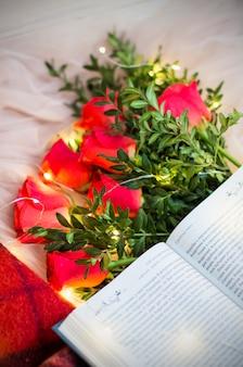 Composição: rosas vermelhas com buxo, um livro, uma guirlanda e um cobertor vermelho.