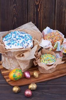 Composição rústica de páscoa. bolos de férias da páscoa com ovos na placa de madeira.