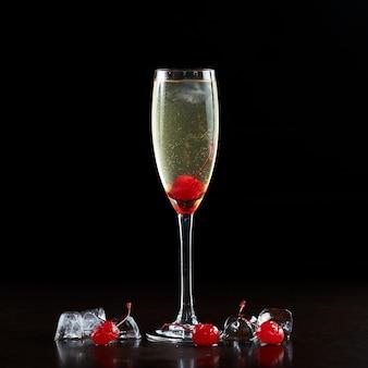 Composição simples de copo de coquetel de cristal alto e elegante com bebida de champanhe transparente e refrescante, cerejas vermelhas maduras e cubos de gelo isolados no fundo preto. proporção da imagem 1: 1
