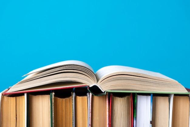 Composição simples de livros de capa dura, livros crus na mesa do deck de madeira e azul
