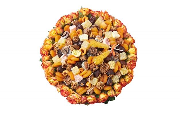 Composição sob a forma de um buquê de frutas secas laranja e amarelas com nozes em um fundo branco