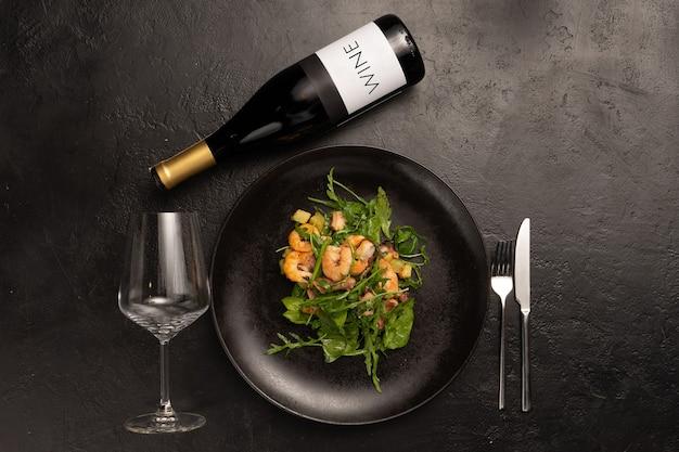 Composição sobre o tema da decoração de um menu de restaurante com aperitivos de salada, uma garrafa de vinho, uma taça e talheres sobre uma mesa de pedra preta.