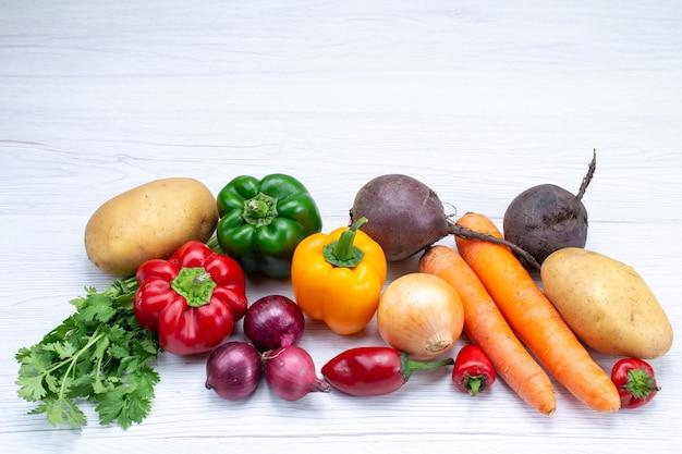 Composição vegetal com legumes frescos, verdes, cenouras, cebolas e batatas na mesa