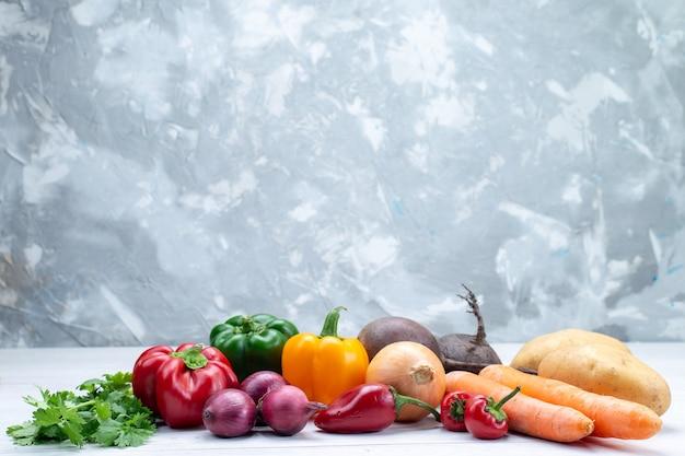 Composição vegetal com vegetais frescos, verdes, cenouras e batatas na mesa de luz