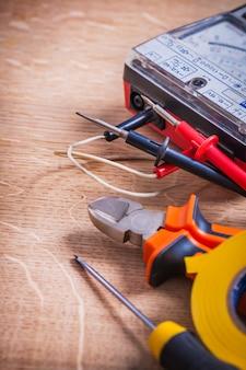 Composição vertical ferramentas elétricas pinças multímetro testador chave de fenda rolo fita isolante na placa de madeira