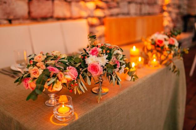Composições de flores na mesa de casamento em decorações de casamento de estilo rústico com as próprias mãos