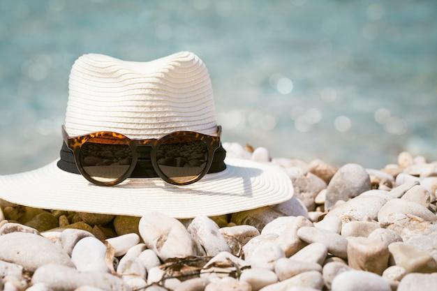 Composições de verão com chapéu de mulher e óculos de sol na praia