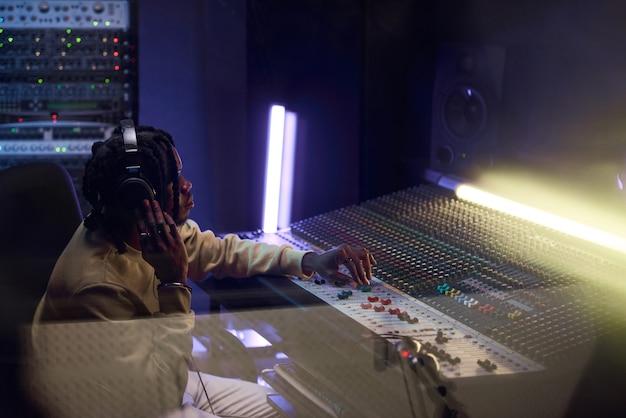 Compositor africano em fones de ouvido usando teclado musical para escrever uma nova música no estúdio de gravação