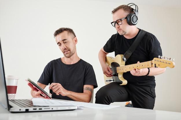 Compositor mostrando música ao guitarrista