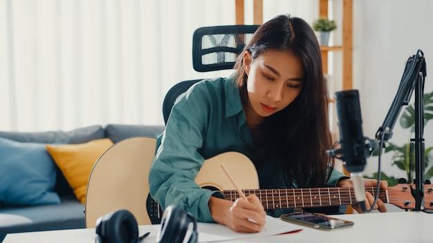 Compositora de música asiática feliz tocando violão e ouvindo música no smartphone