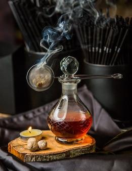 Composto vermelho em uma jarra de vidro e vapor de aroma.