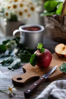 Compota caseira de maçãs de verão em uma mesa de madeira perto da janela com camomila selvagem na jarra