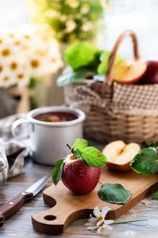 Compota caseira de maçãs de verão em uma mesa de madeira perto da janela