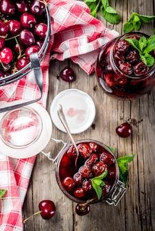 Compota de cereja e menta preservada caseira, com cerejas frescas no espaço de cópia de fundo de madeira velho rústico