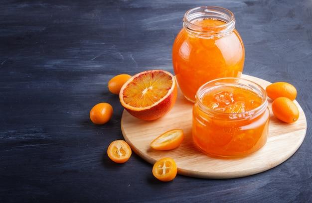 Compota de laranja e kumquat em uma jarra de vidro com frutas frescas em madeira preta