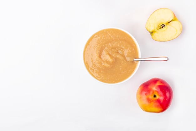 Compota de maçã caseira fresca. conceito de nutrição adequada e alimentação saudável. comida orgânica e vegetariana. bacia branca com purê de frutas na tela e corte as maçãs na mesa.