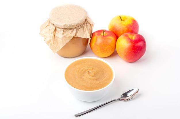 Compota de maçã caseira fresca em tigela branca e jarra com purê de frutas na mesa branca. o conceito de nutrição adequada e alimentação saudável. comida orgânica e vegetariana. comida de bêbe