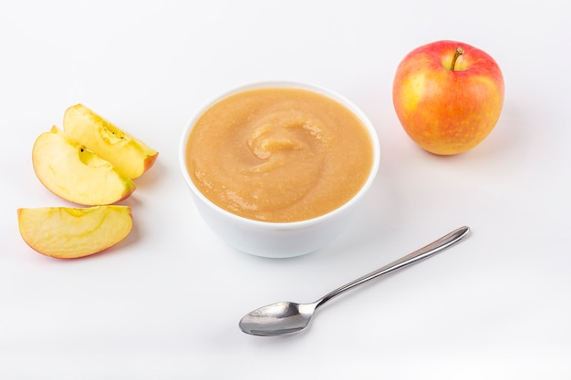 Compota de maçã caseira fresca. o conceito de nutrição adequada e alimentação saudável. comida orgânica e vegetariana. bacia branca com purê de frutas na tela e corte as maçãs na mesa. comida de bêbe.
